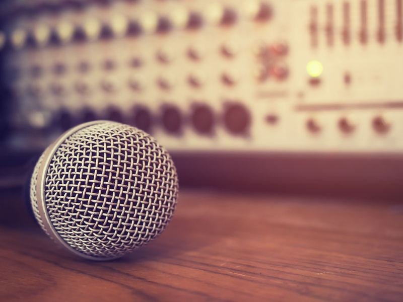Vintage style photo of the microphone in recording studio .